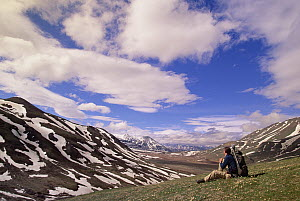 Alaska Range in spring snow, photographer resting in valley below mountains, Denali National Park and Preserve, Alaska - Yva Momatiuk & John Eastcott