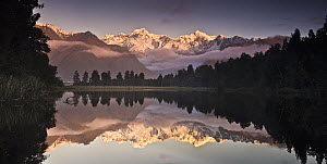 Mount Cook and Mount Tasman reflected in Lake Matheson at sunset near Fox Glacier, New Zealand - Colin Monteath