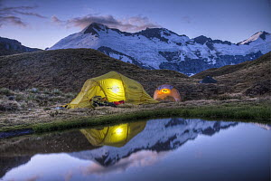Campers read in tents lit by flashlight, Cascade Saddle, Mount Aspiring National Park, New Zealand - Colin Monteath