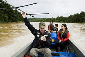 Sunda Clouded Leopard (Neofelis diardi) researcher Andrew Hearn radio tracking from boat with other biologists, Kinabatangan River, Sabah, Borneo, Malaysia - Sebastian Kennerknecht