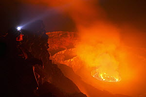 Man looking into crater at night, Mount Nyiragongo, Virunga National Park, Democratic Republic of the Congo - Vincent Grafhorst