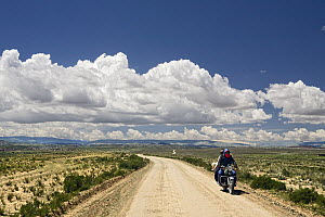 Man and woman riding motorcycle through dry puna, Andes, western Bolivia  -  Sebastian Kennerknecht
