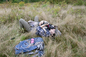Domestic Dog (Canis familiaris) named Skye, a scent detection dog with Conservation Canines, relaxing with field technician Suzie Marlow, Adirondack Mountains, New York - Jaymi Heimbuch