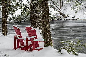 Adirondack chairs along river in winter, Mersey River, Kejimkujik National Park, Nova Scotia, Canada - Scott Leslie