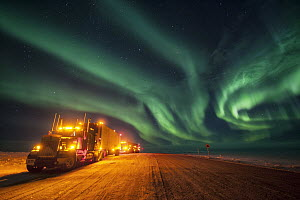 Northern lights over trucks on Dalton Highway which is used to service oil fields in Prudhoe Bay, Alaska  -  Peter Mather