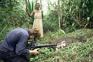 """Cameraman Martin Dohrn filming sow birth watched by local woman, Papua New Guinea, for tv series """"Lifesense""""  -  John Downer"""