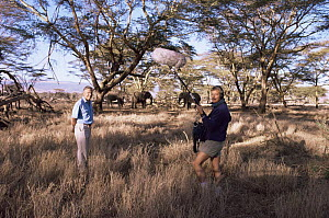 David Attenborough with sound recordist on location in Kenya, standing near elephant herd, about to do a piece to camera - Keith Scholey