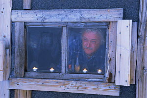 Camerman Martin Saunders, looking out of the Texas Bar hut, home for film crew on location for Polar Bear programme, Svalbard, Norway. 1996  -  Mats Forsberg