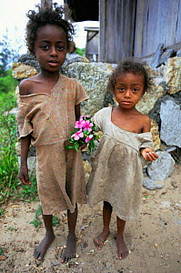 Two Malagasy children holding posie of Rosy Periwinkles {Catharanthus roseus}, southern Madagascar - Nick Garbutt