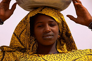 Portrait of Falani woman in traditional clothing, with bowl on her head, Mali, West Africa  -  Grant McDowell