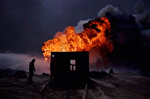 Burning oil well with water control from heat-shielding shed (post Gulf war). Kuwait, Arabia  -  Ross Couper-Johnston