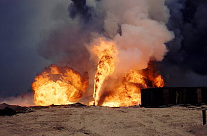Burning oil well with water control from heat-shielding shed (post Guld war). Kuwait, Arabia  -  Ross Couper-Johnston