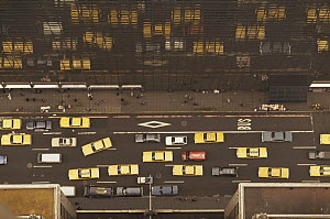 Aerial view of yellow taxi cabs and other traffic reflected in glass of skyscraper in New York city, USA  -  Martin Dohrn