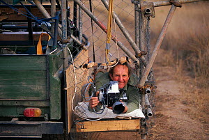 Mike Richards filming in cage beside vehicle Africa  -  John Downer