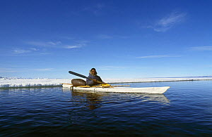 Inuit hunter in kayak with seal skin float, Canadian Arctic  -  DOC WHITE