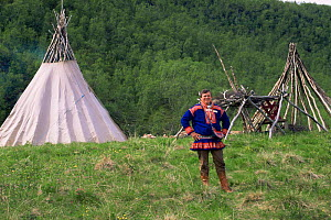 Sami man in traditional clothing, standing in front of lavvu teepee, Lapland, Norway, Europe. 1997.  -  Pete Oxford