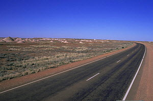 Stewart highway through Outback with spoil mounds from opal mining, Coober Pedy, South Australia - WILLIAM OSBORN