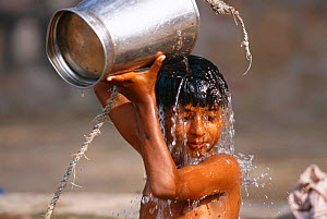 Young boy taking a bucket bath at well, Keoladeo Ghana NP, Bharatpur, Rajasthan, India  -  Bernard Castelein