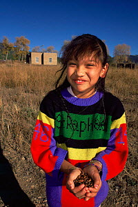 Native American girl holding Pixon nuts, Taos Pueblo, New Mexico, USA 1990  -  John Cancalosi