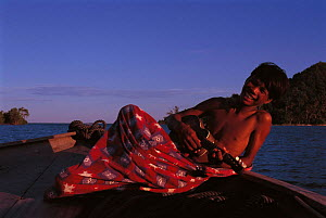 Bajau boy playing banjo, Malaysia. Bajau people live in houses on stilts or are nomadic in houseboats. 2000  -  Jurgen Freund