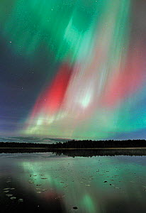 Aurora borealis colours in night sky over lake, northern Finland - Jorma Luhta