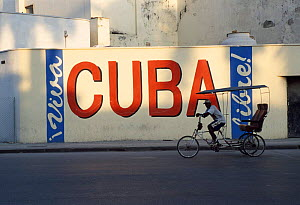 Man on rickshaw cycling past Cuba sign, Old-Havana, Havana, Cuba Caribbean  -  Gavin Hellier