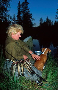 Fisherman with dog at lake in evening. Trout fishing. Norway  -  Asgeir Helgestad