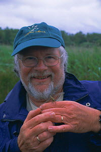 Television presenter Bill Oddie with newly emerged dragonfly on hand. Norfolk Broads, UK. 2003 - Martin H Smith