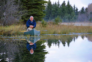 Sir David Attenborough in canoe during filming of 'Life of Mammals' 2002. Wyoming, USA  -  Neil Lucas