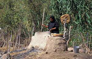Marsh arab woman cooking at traditional oven Iran / Iraq border, 1998 - NIGEL MARVEN