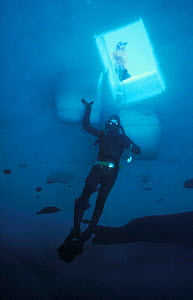 Diver under access hole that has been cut in the sea ice, Antarctica 1987 - Doug Allan