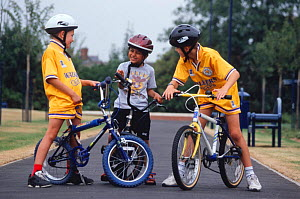 Three children standing with bikes on path, Leicester, England  -  Julia Bayne