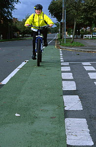 Boy cycling home from school in cycle lane on road, UK  -  Julia Bayne