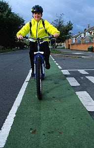 Boy cycling home from school in cycle land on road, UK  -  Julia Bayne