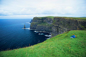 People looking out over the Cliffs of Moher, County Mayo, Southern Ireland  -  DAVID TIPLING
