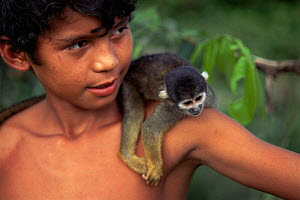 Boy with pet Blackish squirrel monkey {Saimiri vanzolinii} Amazonas, Brazil  -  Luiz Claudio Marigo