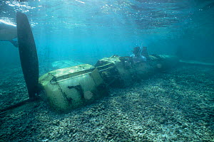 Diver sitting in wreck of WWII Japanese fighter plane, Palau, Micronesia  -  Doug Perrine