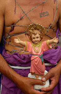 Cucurucho carries statue of Jesus and wraps barbed wire around his chest to share in suffering. Good Friday parade, Quito, Ecuador. - Pete Oxford
