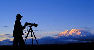 Silhouette of nature photographer in front of Mount McKinley, Denali NP, Alaska, USA.  -  Philippe Clement