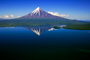 Kronotsky Volcano with reflection in Kronotsky Lake - the largest freshwater lake on the Kamchatka peninsula, formed after the eruption of two volcanoes created a lava barrier that water could not bre... - Igor Shpilenok