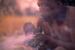 Jo / Hoan bushman making fire by traditional method, Bushmanland, Namibia. 1996  -  Owen Newman