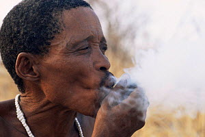 Jo / Hoan bushman smoking traditional pipe, Bushmanland, Namibia. 1996  -  Owen Newman