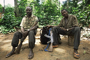 Members of the Wildlife Conservation Society anti-poaching patrol team relaxing with their AK47 and rifle guns beside them, Dzanga-Sanga Bai, Bayanga, Central African Republic, 2003  -  James Aldred