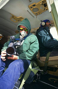 Doug Allan, cameraman, filming for BBC 'Andes to Amazon' wearing oxygen mask for filming aerials out of the open door of Cessna plane at 6500m, Bolivia, 1997 - Doug Allan