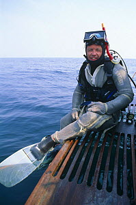 Doug Allan, cameraman, preparing to dive with chain mail suit for shark protection, for National Geographic, 1995  -  Doug Allan