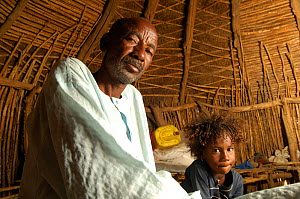 Elderly Fulani man with his grandchild in traditional hut, South Mauritania, West Africa, 2005  -  Laurent Geslin