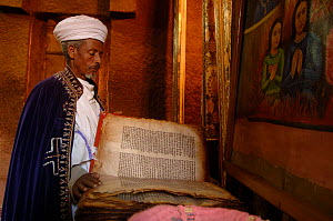 Orthodox priest reading from a Holy book, Beita Gabrielle church, Lalibela, Ethiopia, 2006  -  Laurent Geslin
