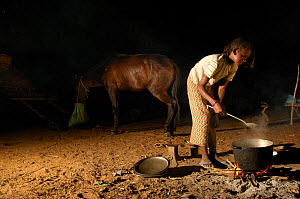 Fulani woman cooking at night, horse in background, North Senegal, West Africa, 2005  -  Laurent Geslin