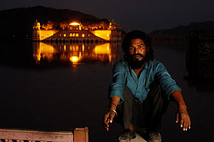 Indian with the Jai Mahal (Lake Palace) in the background floodlit at night, Jaipur, Rajasthan, India 2006 - Laurent Geslin