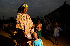 Fulani woman feeding milk to her child at dawn after milking the cattle, North Senegal, West Africa, 2005  -  Laurent Geslin